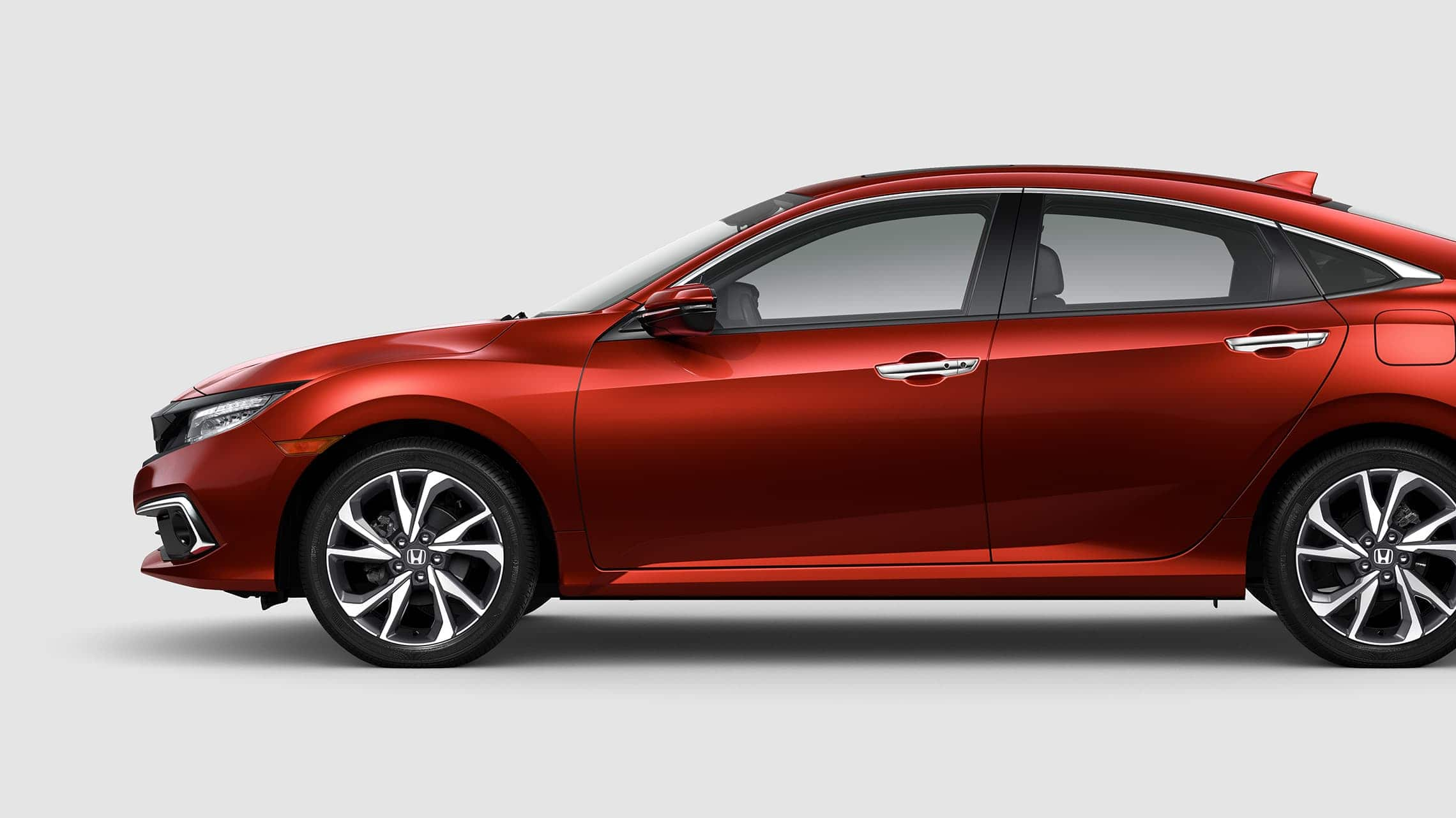 Driver-side profile view of the 2020 Honda Civic Touring Sedan in Molten Lava Pearl.