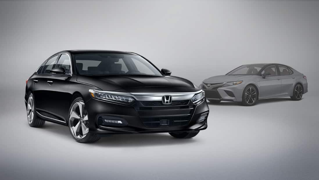 Front passenger-side view of the 2020 Honda Accord Touring 2.0T parked next to competitor vehicle Toyota Camry.