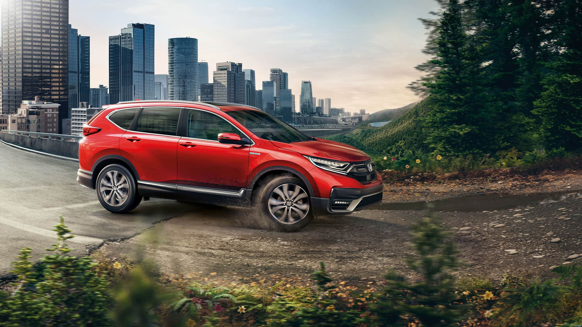 Passenger-side view of the 2020 CR-V Hybrid Touring in Radiant Red Metallic, driving from a city into a forest.